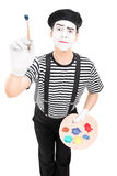 Male mime artist holding a paintbrush. And a color pallet isolated on white background royalty free stock photos