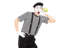Male mime artist listening through wall with a cup Stock Images