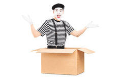 Male mime artist sitting in carton box. Male mime artist sitting in a carton box and gesturing with hands isolated on white background Royalty Free Stock Photography