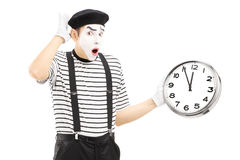 Male mime holding a clock and gesturing late. Isolated on white background Stock Images