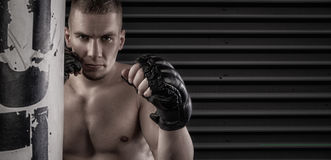 Male mma fighter in gloves dark background. Mma fighter in fighing stance near punching bag royalty free stock photography