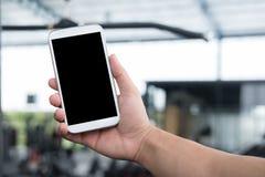 male& x27; mobiltelefon för s-handhåll i idrottshall man med smartphonen i passform Royaltyfria Bilder