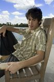 Male model 1. Young male model posed on a seat in front of a beautiful lake Royalty Free Stock Photos