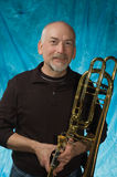 Male model. Mature man posing with trombone in front of portrait backdrop Stock Images