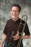 Male model. Mature man posing with trombone in front of portrait backdrop Royalty Free Stock Photo