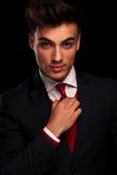 Male model in black suit fixing his red tie. Close portrait of handsome male model in black suit fixing his red tie while looking at the camera in dark studio Stock Photos