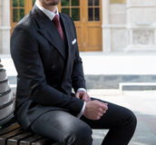 Male model. In a black suit, sitting on a bench Stock Image