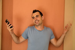 Male model with cell phone in hand showing a whatever attitude Stock Photography
