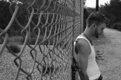 Male Model on Chainlink. Male model leaning on a chain link fence in a park Stock Photo