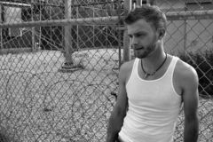 Male Model on Chainlink and Wire. Male model leaning on a chain link fence in a park Royalty Free Stock Photography