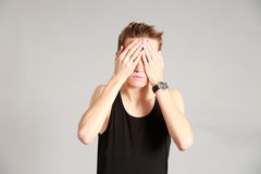 Male model covering eyes with hands Stock Photo