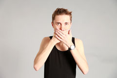 Male model covering mouth with hands. Fashion shot of thin young male model in studio covering mouth with hands stock photos