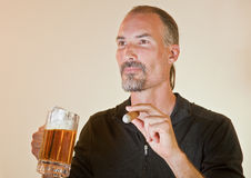 Male Model Enjoying A Beer And A Cigar Royalty Free Stock Photography
