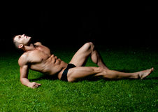Male model on the grass. Muscled male model posing on the grass Royalty Free Stock Photo