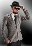 A young man in a gray jacket  hat sunglasses Stock Image