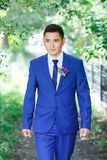 Male model, the groom portrait in a blue suit with a boutonniere among the green foliage on a wedding day. royalty free stock photos