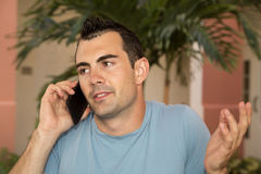 Male model on his cell phone shrugging his shoulders questioning Royalty Free Stock Photos