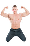 Male model on his knees flexing strong arms Royalty Free Stock Photos