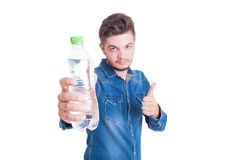 Male model holding water and showing like gesture. Male model holding bottle of water and showing like gesture or thumb-up on white background Royalty Free Stock Image