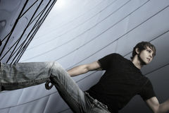 Male model in horizontal pose. Male model in jeans againstfuturistic metal background Royalty Free Stock Photos
