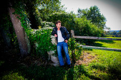 Male Model leaning on a stone wall. Stock Image