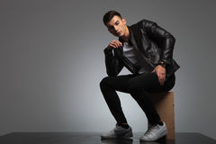 Male model in leather jacket posing seated while thinking Stock Image