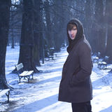 Male model looking back, in a cold winter scenery. Male model in jacket and warm sweeter walking via blue park alley covered in snow background Royalty Free Stock Images