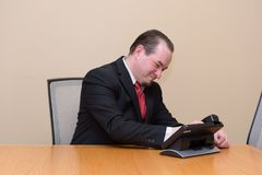 Business man in a boardroom. Male model in a nice suit, seated in a boardroom angrily slamming the phone down Royalty Free Stock Images