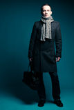 Male model over dark blue background. Portrait of a fashionable male model wearing trendy clothing (coat, scarf, jeans) and black leather bag over dark blue stock photo