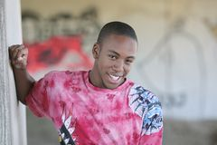 Male model posing. A young African American male model smiling outdoors in front of graffiti Stock Photography