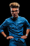Male model posing wearing jeans, denim shirt and glasses. Beautiful male model posing wearing jeans, denim shirt and glasses posing with hands on waist in dark Royalty Free Stock Photo