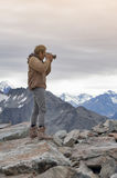 Male model posts at the top of snowcapped mountain peak around Aoraki Mount Cook and Mount Cook National Park Royalty Free Stock Photos