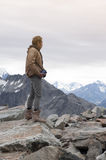 Male model posts at the top of snowcapped mountain peak around Aoraki Mount Cook and Mount Cook National Park Royalty Free Stock Photography
