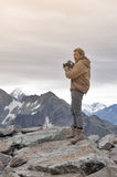 Male model posts at the top of snowcapped mountain peak around Aoraki Mount Cook and Mount Cook National Park Stock Photos