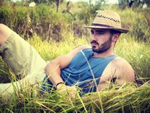 Male model relaxing, laying in a field stock photo