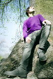 Male model resting on a large tree trunk Royalty Free Stock Photography