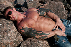 Male model on the rocks. Muscled male model on the rocks Royalty Free Stock Photography