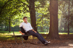 Male model sitting on a bench. In the park alley at sunrise Stock Photography