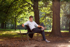 Male model sitting on a bench. In the park alley at sunrise Stock Images