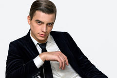Male model sitting in a business suit black studio Stock Photo