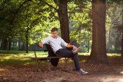 male model sitting för bänk Arkivbilder