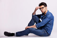 Male model sitting on grey background and thinking Royalty Free Stock Photography