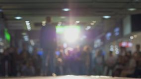 Male model in solid suit and shoes walk podium during fashion show in backlight on background blurred audience
