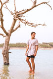 Male model stood under a dying tree in a flooded lake. Royalty Free Stock Photo