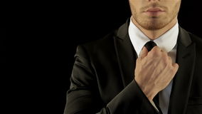 Male model in stylish suite corrects his necktie stock video footage