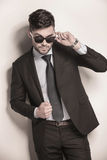 Male model in suit and tie taking off his sunglasses Stock Photos