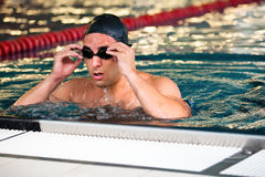 Male model swimmer with black goggles. And cap resting between laps Royalty Free Stock Photo