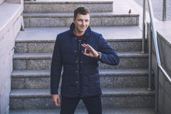 Male model in trendy modern youth warm jacket in the urban lands Stock Photos
