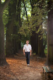 Male model walking through park alley. Happy and attractive man in the park at sunrise Stock Images