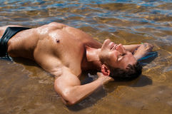 Male model in the water. Muscled male model posing in the water Stock Images